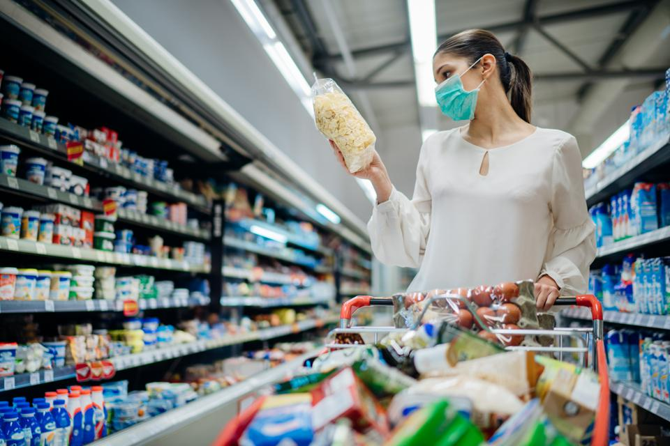 Young person with protective face mask buying groceries/supplies in the supermarket.Preparation for a pandemic quarantine due to coronavirus covid-19 outbreak.Choosing nonperishable food essentials