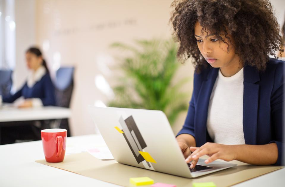 Businesswoman working on laptop at startup