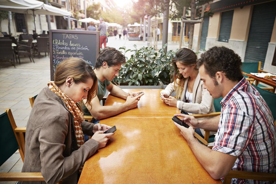 Four friends all looking at their phones at cafe
