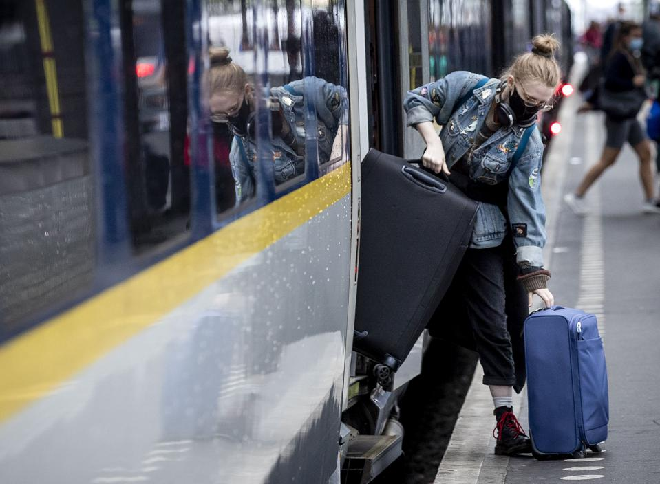 A passenger in a mask carries her luggage as she gets off a Eurostar train in Amsterdam.