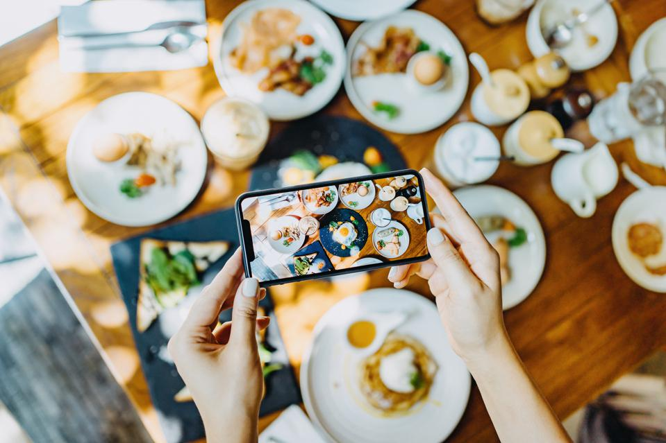 Directly above view of woman's hand taking photo of freshly served brunch with smartphone in an outdoor restaurant against beautiful sunlight
