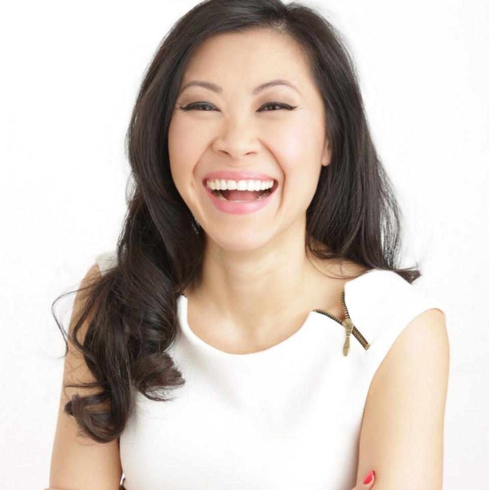 Melissa Leong smiling happily, long hair, arms crossed, wearing a sleeveless white top.