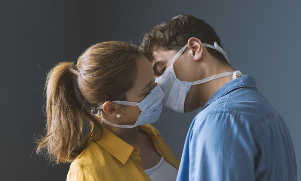 Young couple wearing a protective face mask and kissing