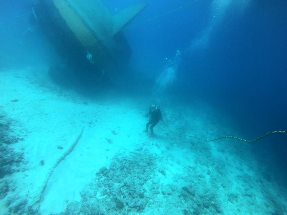Indian Navy diver approaches overturned Sir Gaetan from the rear of the vessel.  The vessel is perched on the shallower coral reef structure at 18 meters depth, which slides to the deep ocean bottom to the right.
