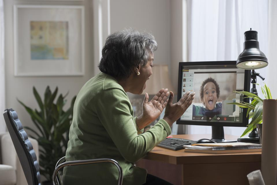 Grandmother videoconferencing with grandson during pandemic.