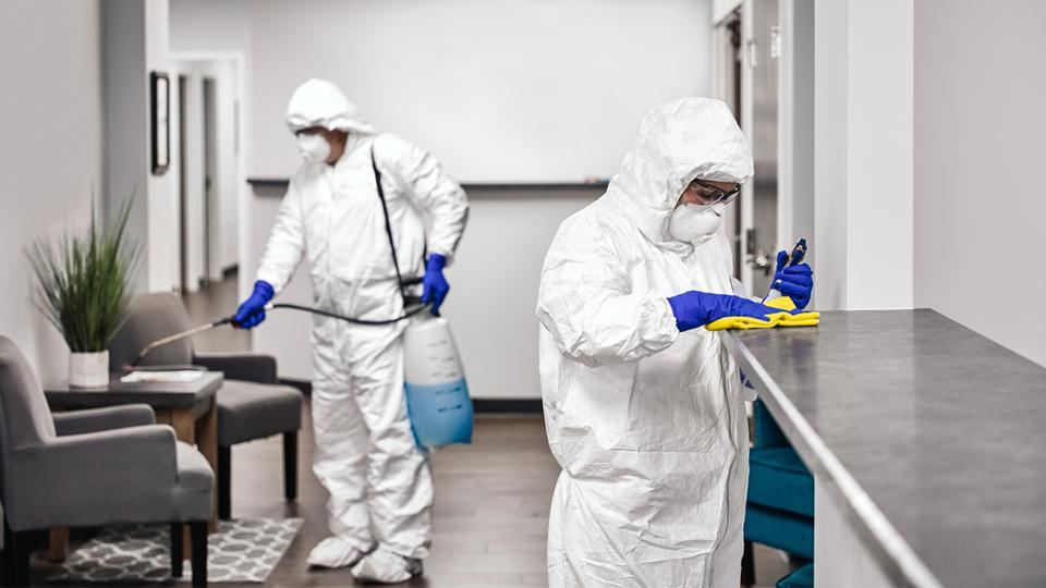 People in white coveralls, masks and gloves sanitize a workspace.