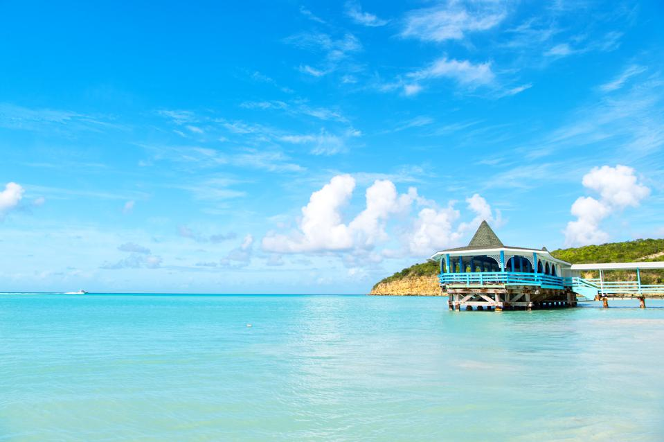 Sea beach with wooden shelter on sunny day in antigua. Pier in turquoise water on blue sky background. Summer vacation on caribbean. Wanderlust, travel, trip. Adventure, discovery, journey