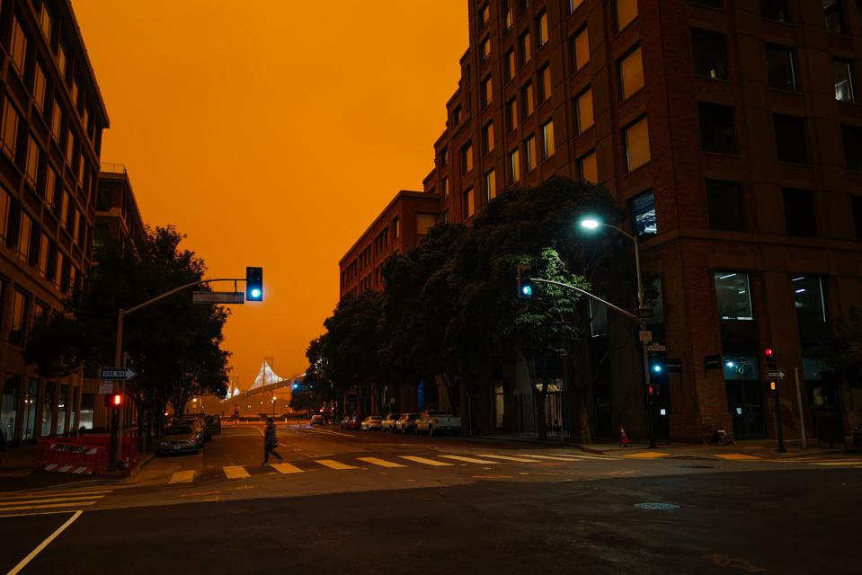 A view of San Francisco. The sky is dark orange from wildfire smoke.