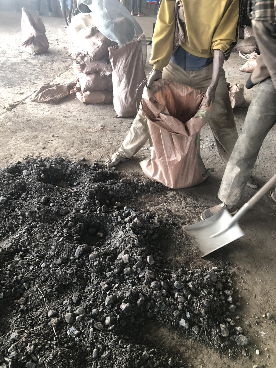 Image of workers shoveling cobalt at a mine in the Democratic Republic of the Congo.