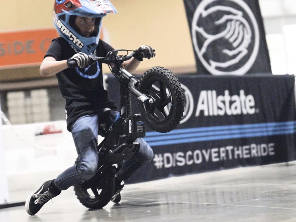 child riding a wheelie on a balance bike