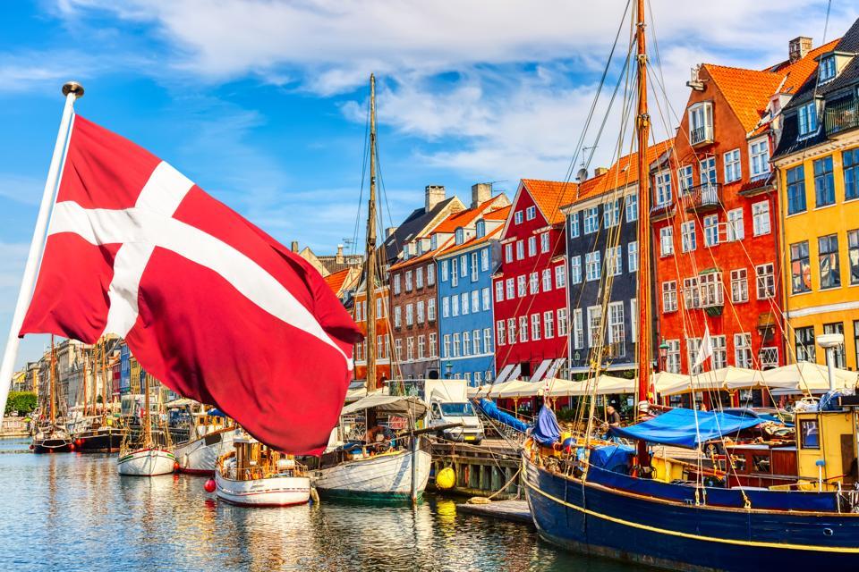 Flag of Denmark and the famous old Nyhavn port in the center of Copenhagen.