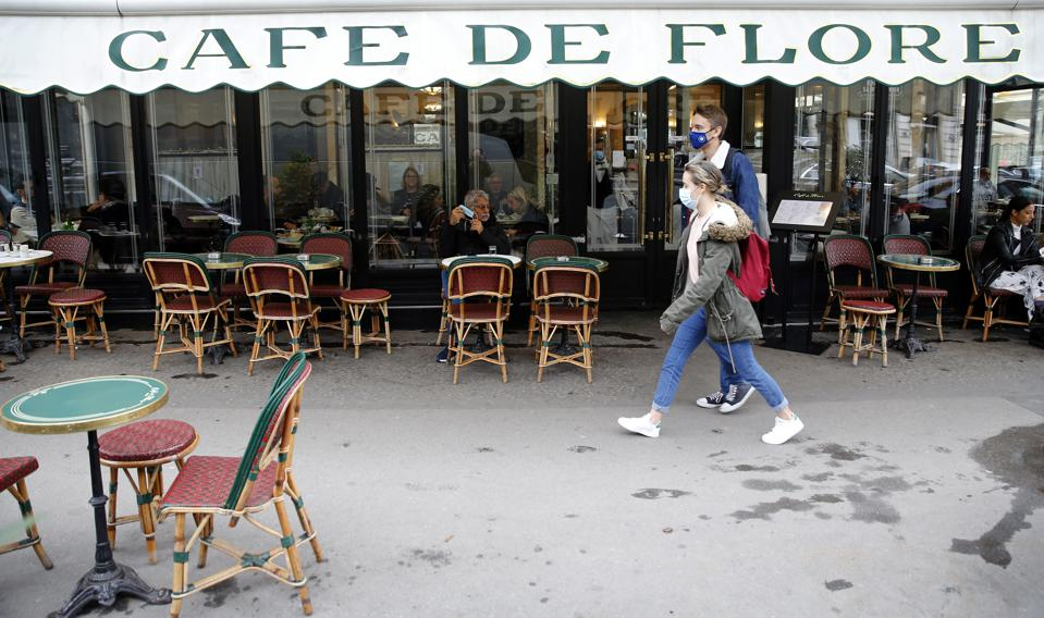 People in masks walk past Paris cafe as bars close As COVID-19 Alert Is Raised To Maximum