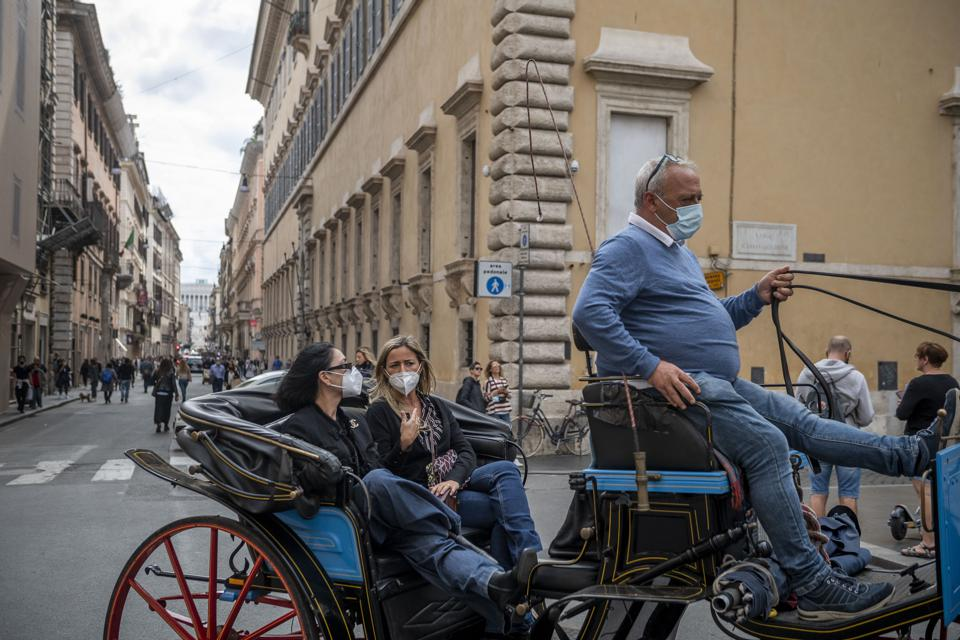 Tourists in masks take a horse ride in Rome Italy