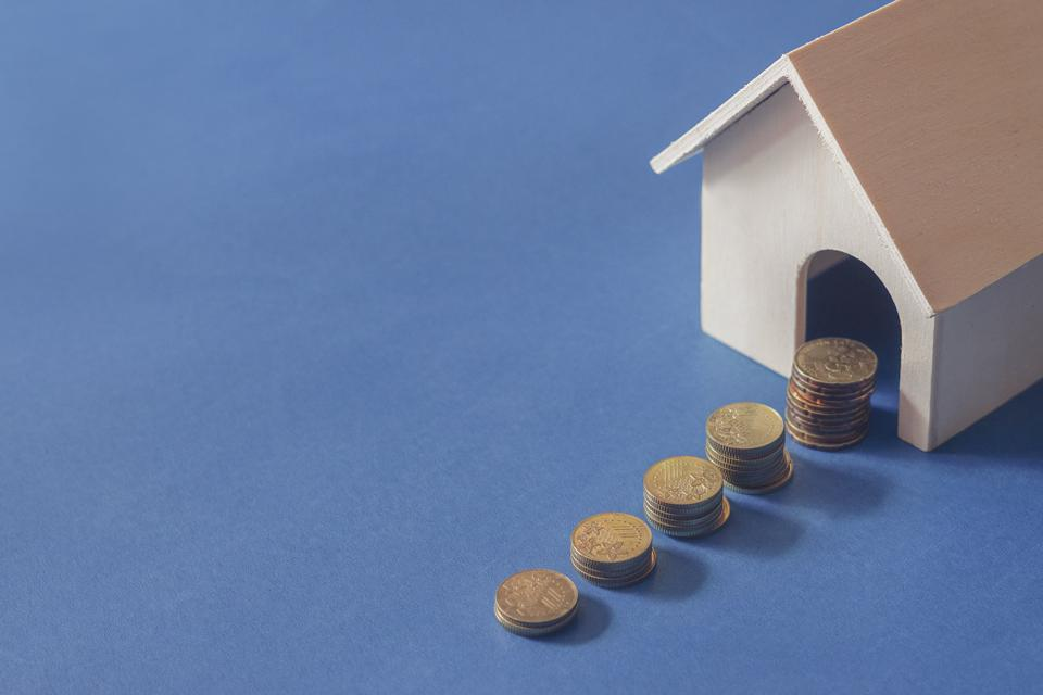 Buying new house concept. Gold coin and toy house on blue background