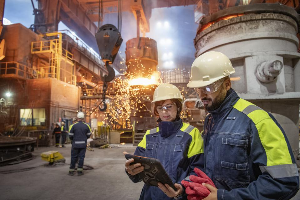 Male and female steelworkers using digital tablet during steel pour in steelworks