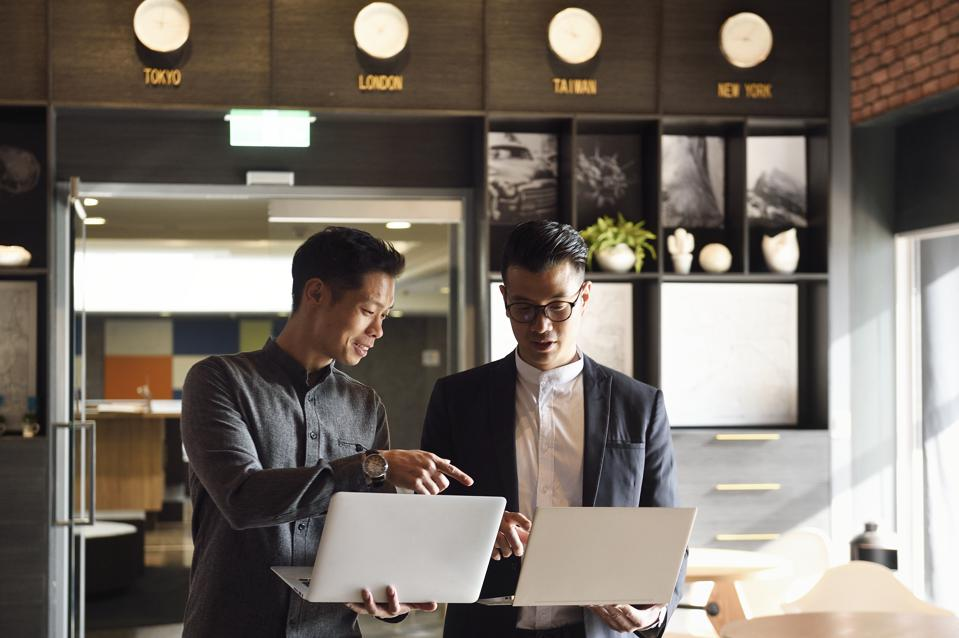 Two handsome Chinese men standing with laptops in an office