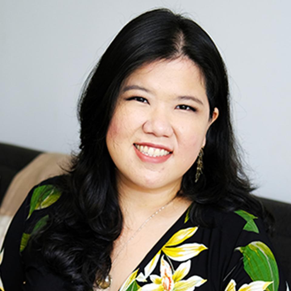 Maria Tan sitting, smiling, long black hair.