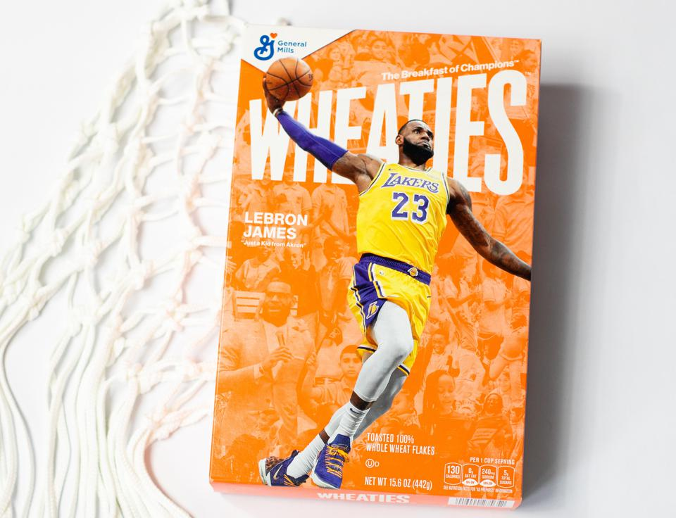 LeBron James soars for a dunk on the front of the Wheaties box with images of staff and students from his I Promise school in the background.