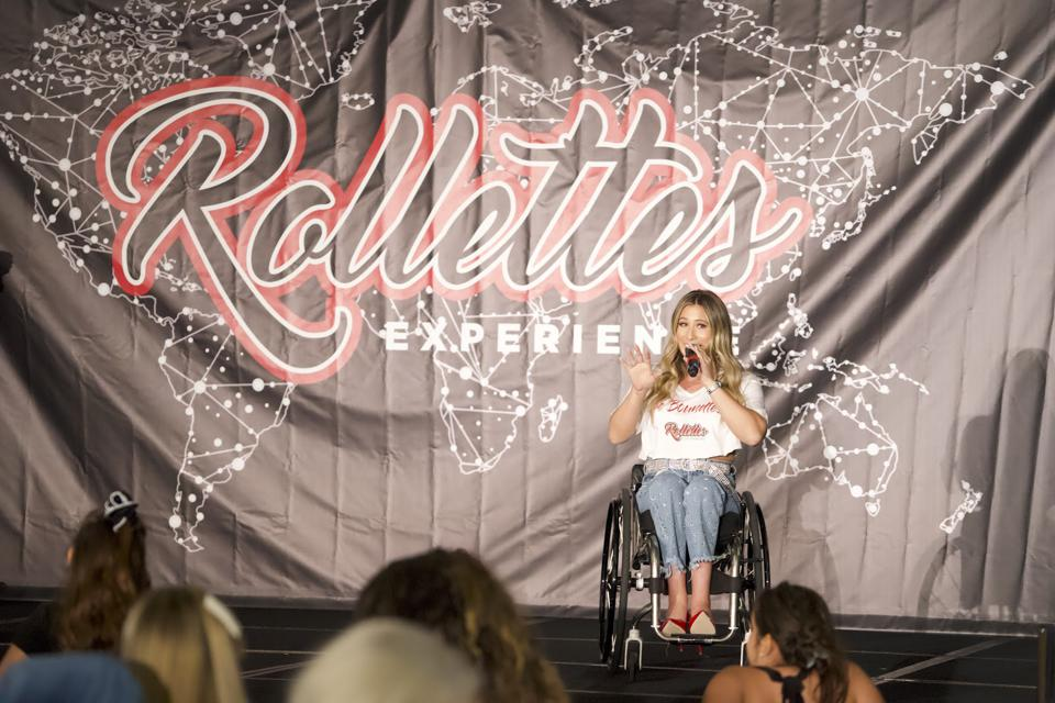 A woman in a wheelchair speaks on stage to an audience at The Rollettes Experience.