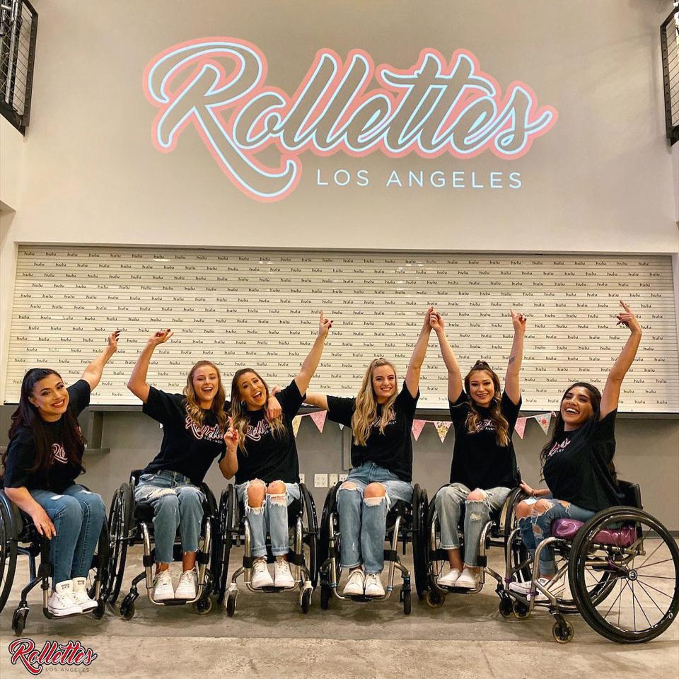 Six women in wheelchairs pose in front of a sign that says Rollettes Los Angeles.