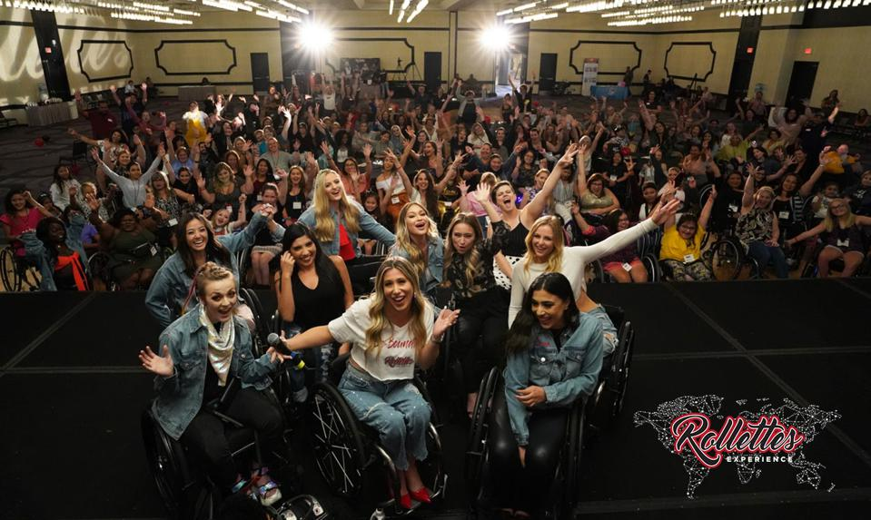 Women in wheelchairs pose on stage with an audience of over 100 people.