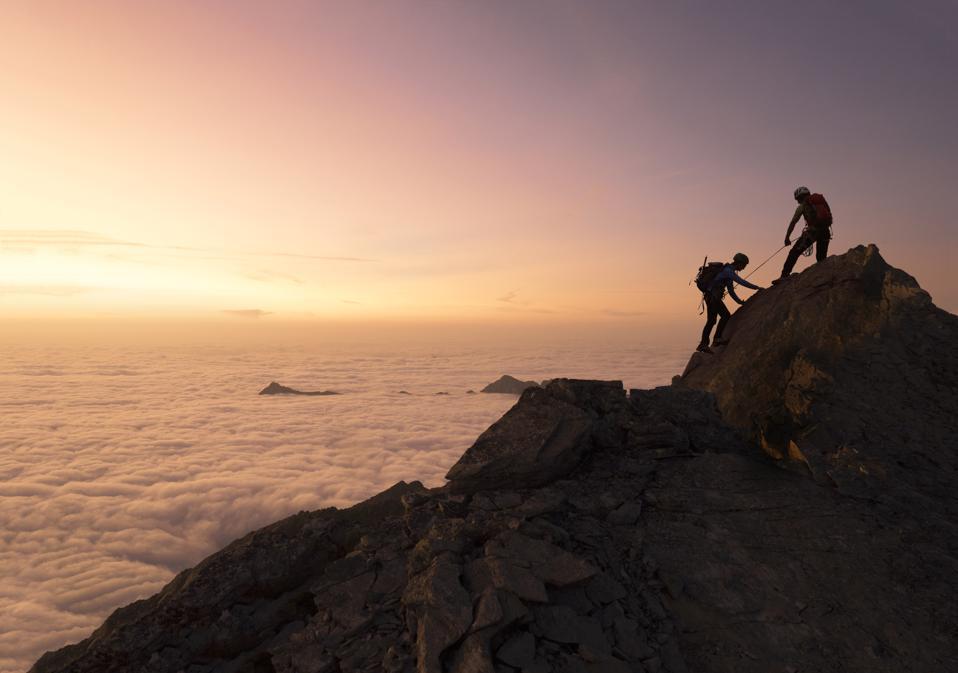 Climbers reaching a mountain top.