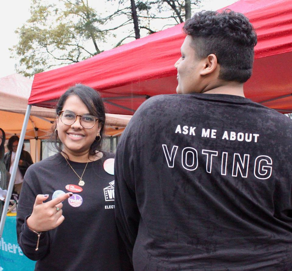 Clarissa stands outside on her campus advocating for youth voting.