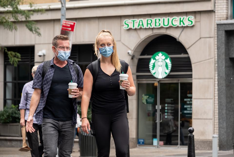 Starbucks customers wearing masks outside a store. (Photo by Noam Galai/Getty Images)