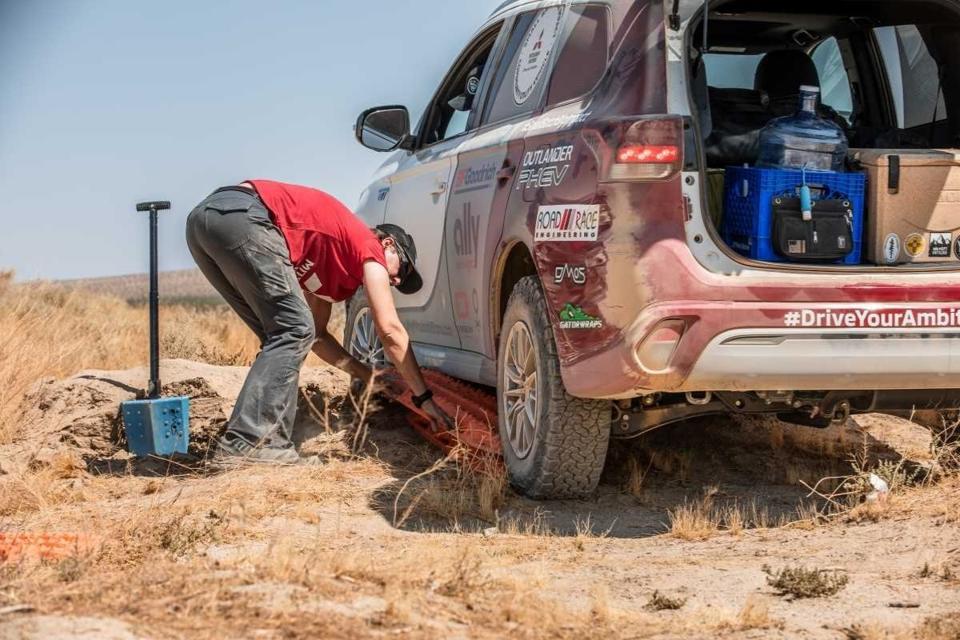 woman fixing car in the desert