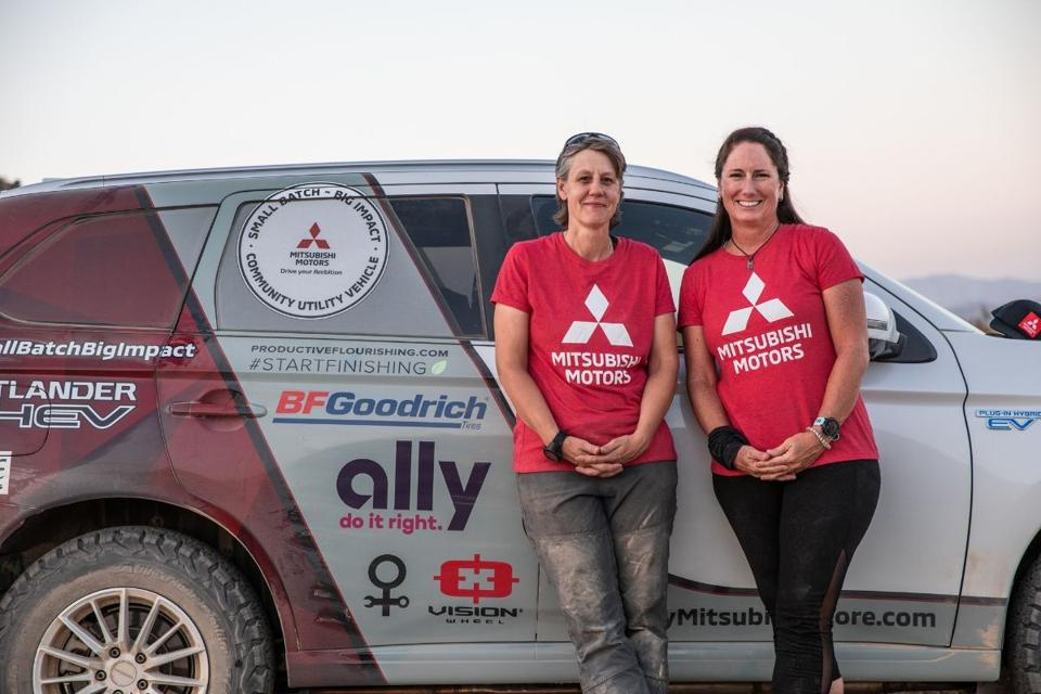 two women in front of Mitsubishi car