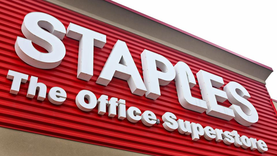 The entrance of a Staples store in Mount Prospect, Illinois, showing the Staples name in a white and red sign.