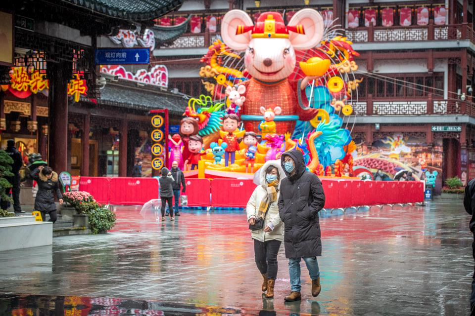 People wearing masks walk past a Chinese New Year display