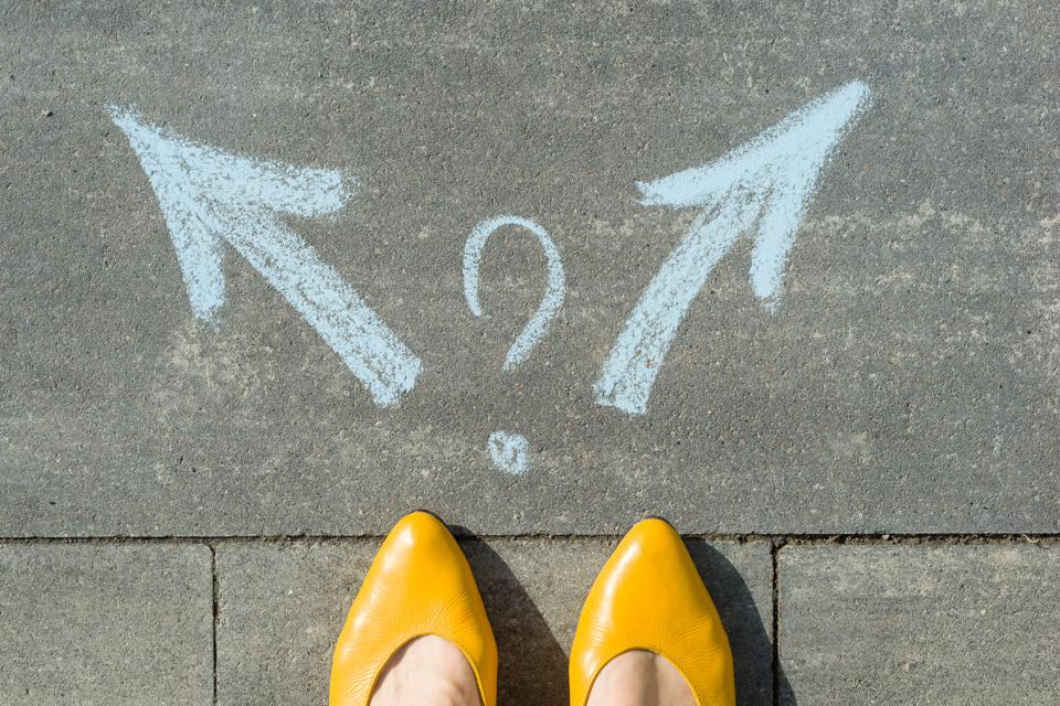 Female legs with 2 arrows and question mark, painted on the asphalt