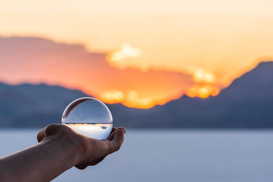 Bonneville Salt Flats colorful landscape bokeh background with hand holding crystal ball near Salt Lake City, Utah and mountain view and sunset