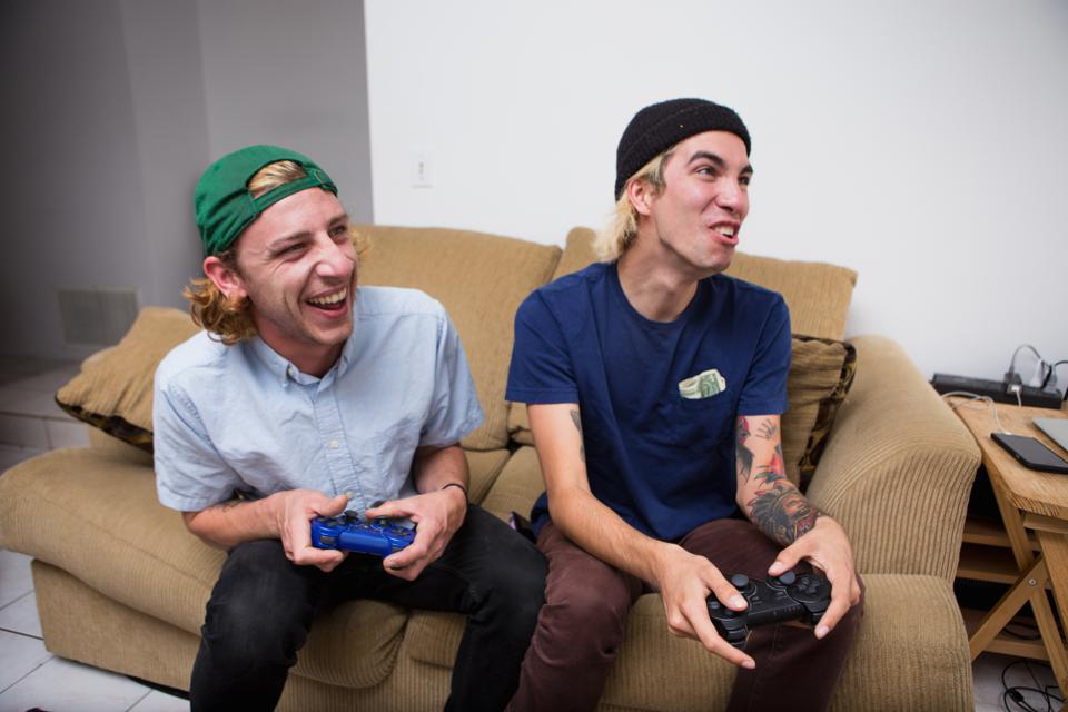 Two young men sitting on sofa, playing video game