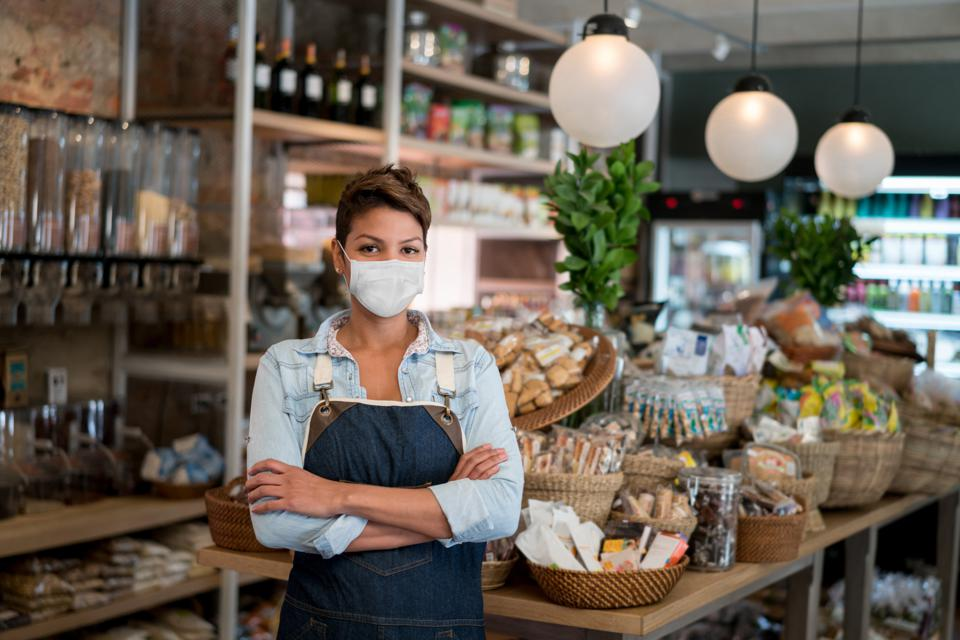 Business owner working at a grocery store wearing a facemask