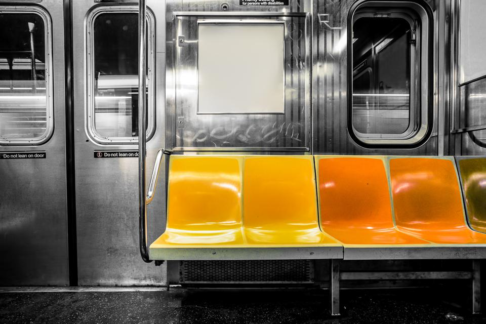 Picture of subway seats against a black and white subway car