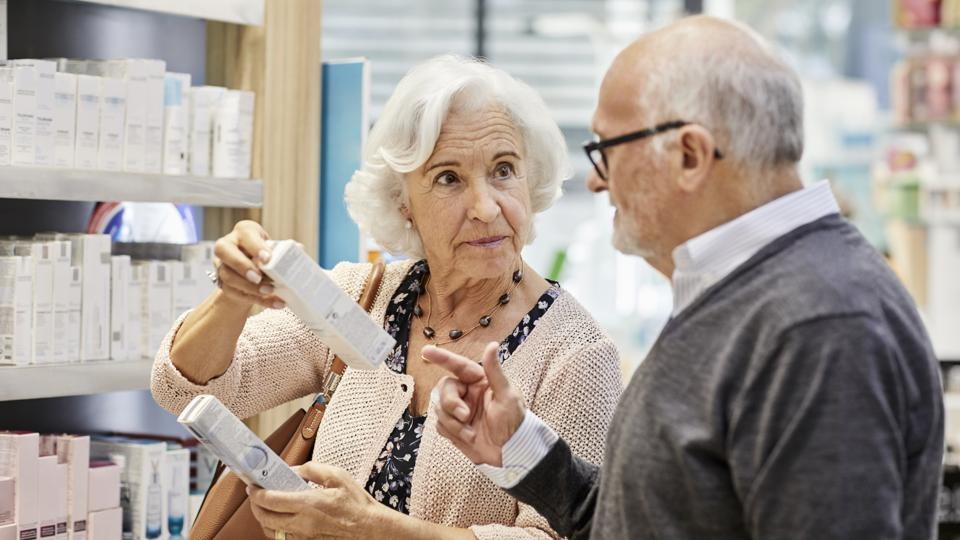 Elderly woman discussing over medicine with man