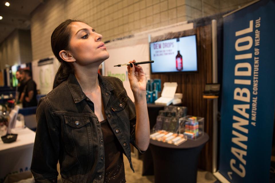 A woman poses while smoking a vape stick