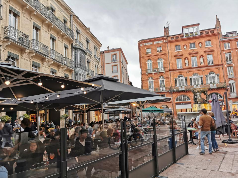 Toulouse residents gather at bars on the Place de la Trinité where establishments have tried to take precautions against COVID.