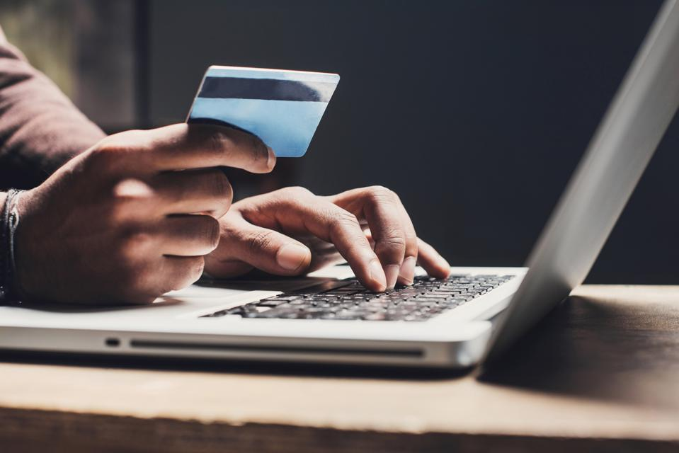 Man shopping online using laptop computer and credit card