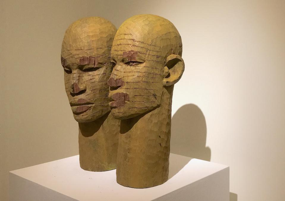 wooden sculptures of two heads