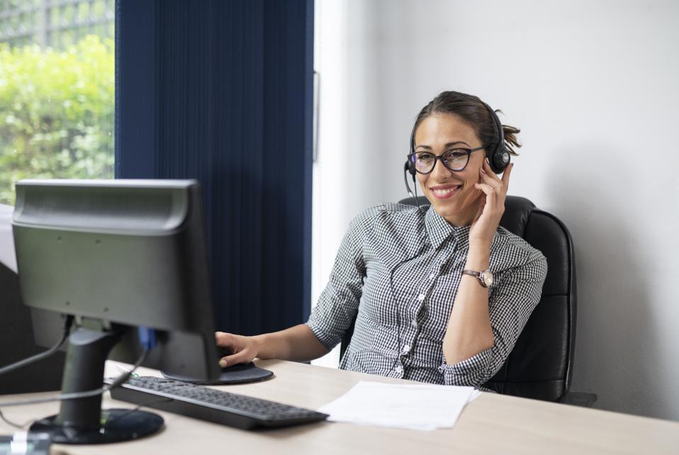 Businesswoman wearing headset in office.