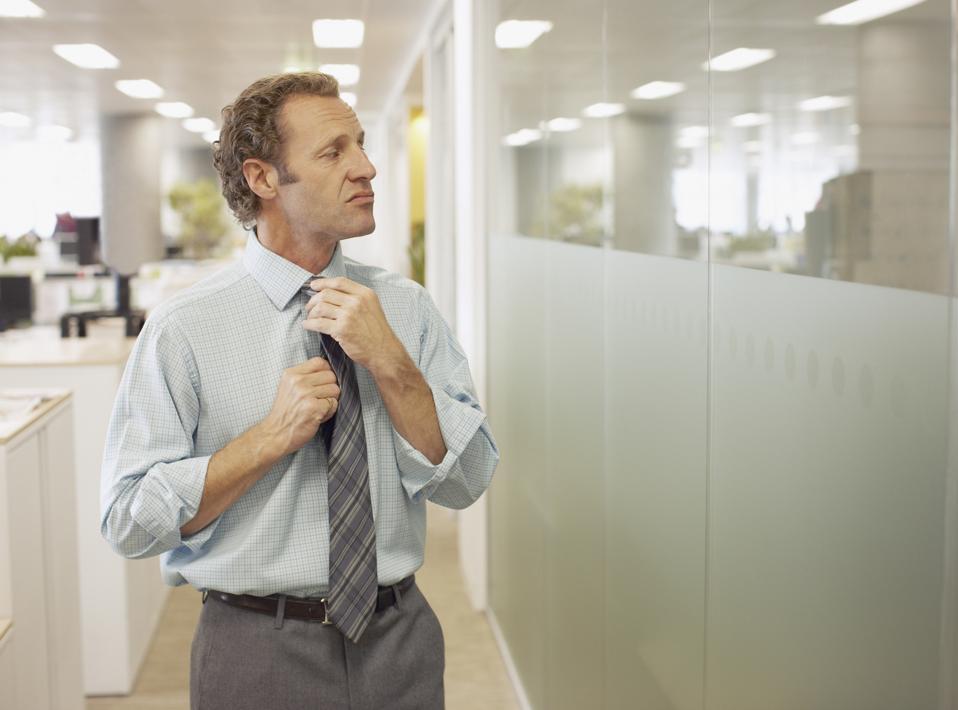 Businessman adjusting tie in office