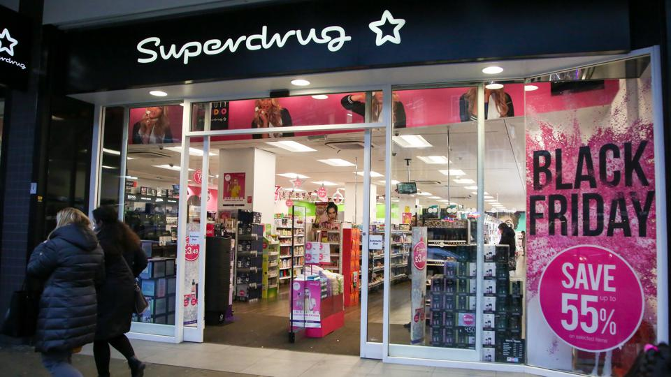 Shoppers are seen walking past the Superdrug store in London...