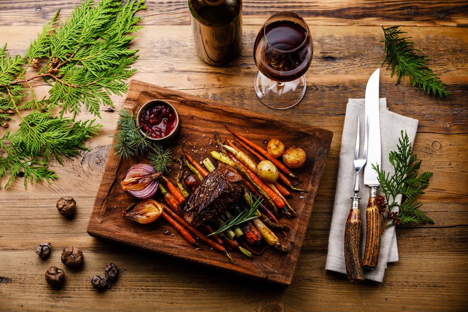 Grilled Venison Steak with baked vegetables and berry sauce and Red wine on wooden background