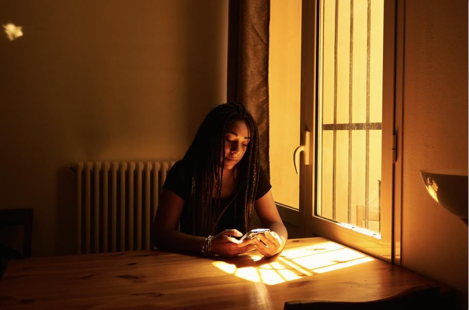 Aisha Coulibali co-founder of Mygrants sitting at a window with the sun shining at the table in front of her while she is looking at her phone