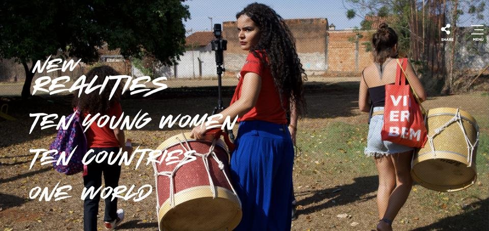 Three young women carrying drums and bags walking away from the camera in a rural area with one turning towards the camera. The words New Realities Ten youong women ten countries one world