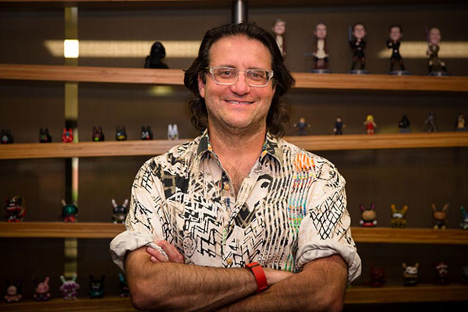A photo of author Brad Feld standing in front of several shelves of figurines.