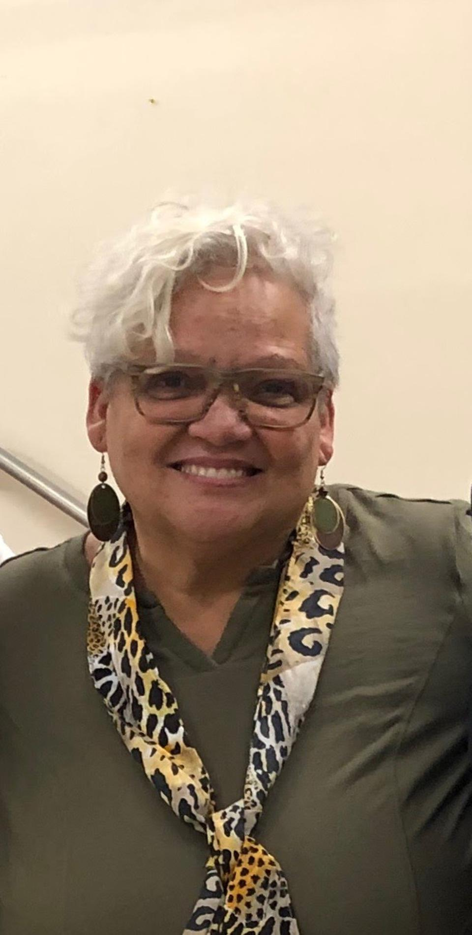 A woman with short white hair and glasses wearing a hunter green top and leopard scarf.